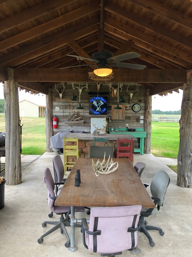 party pavilion with dining, fireplace, and firepit at oak creek ranch hunting lodge in columbus, tx
