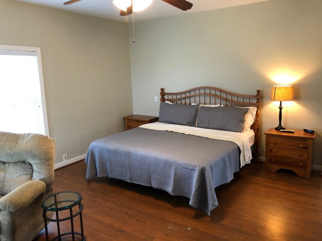 master bedroom with ensuite bath at oak creek ranch hunting lodge in columbus, tx